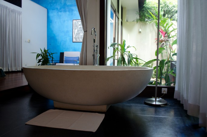A bathtub in the middle of a bedroom. Standard.