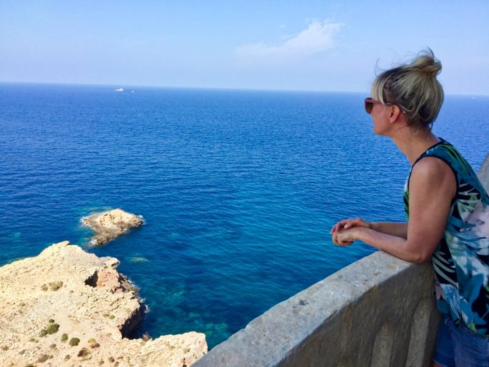 writer looking at the view of the sea from the lighthouse